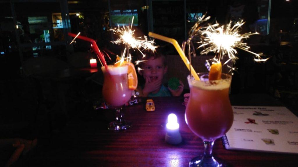 Zwei dekorative Cocktails mit leuchtenden Wunderkerzen. Im Hintergrund sieht man das überraschte Gesicht eines Kindes.