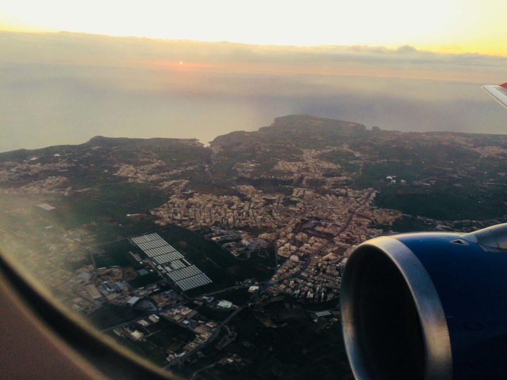 Die Insel Gozo vom Flugzeug aus fotografiert. Im Vordergrund sieht man die Turbine des Flugzeuges und den Rahmen des Fensters.