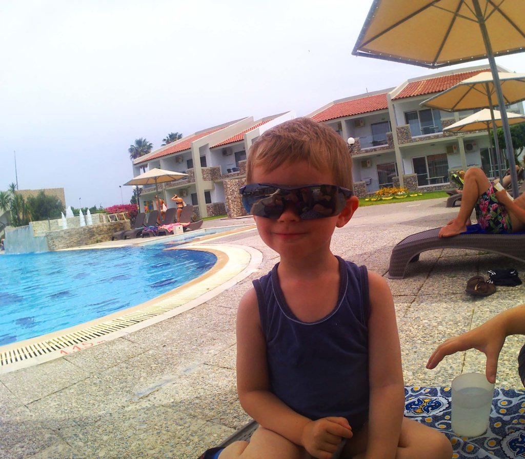 Kind mit Sonnenbrille am Pool.