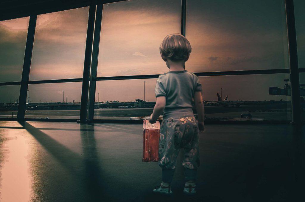 Kind steht mit einen kleinen Koffer im inneren eines Flughafens. im Hintergrund sind durch die Fenster die Flugzeuge zu sehen.