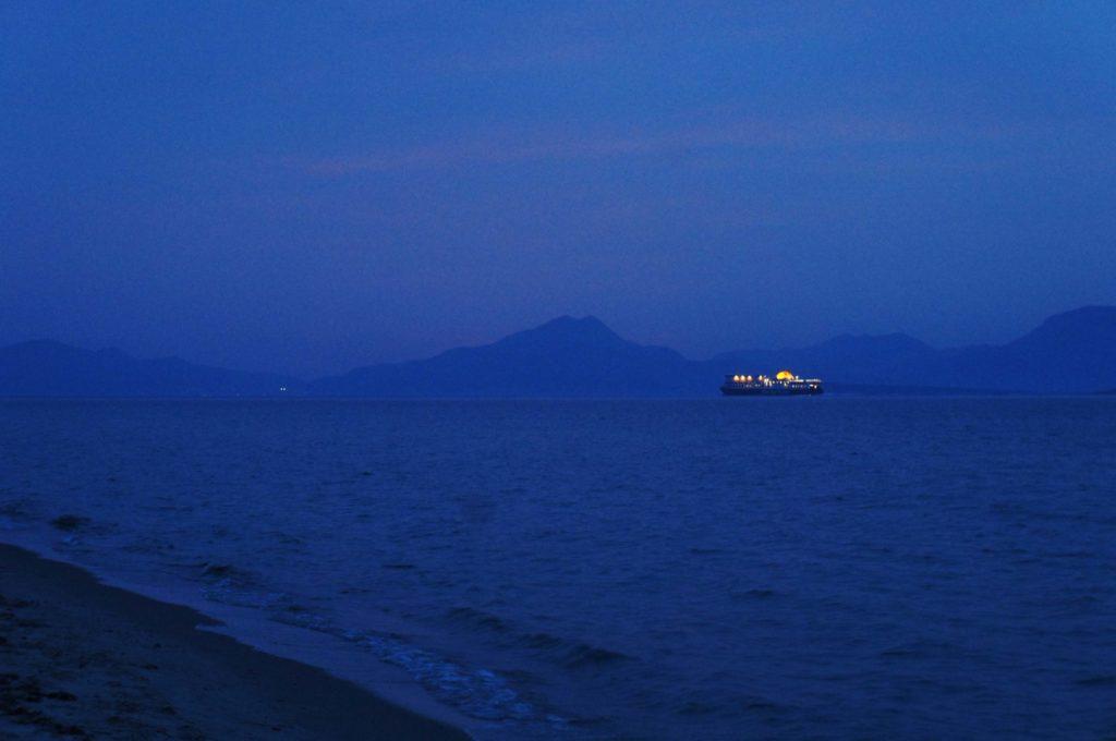 Am Strand von Tigkaki: In der Dämmerung sieht man ein Schiff vor den Bergen der umliegenden Inseln fahren.