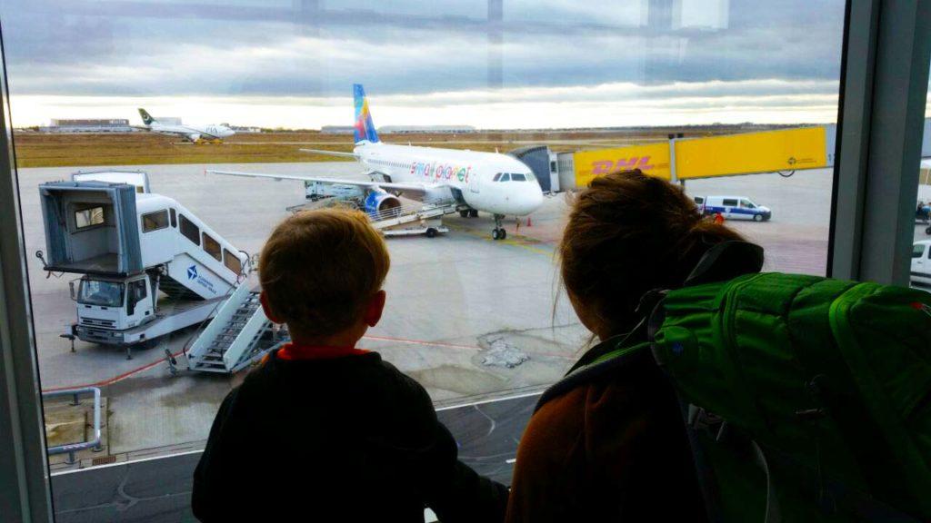 Mutter und Kind schauen durch ein Fenster des Leipziger Flughafens und beobachten wie ein Flugzeug beladen wird.