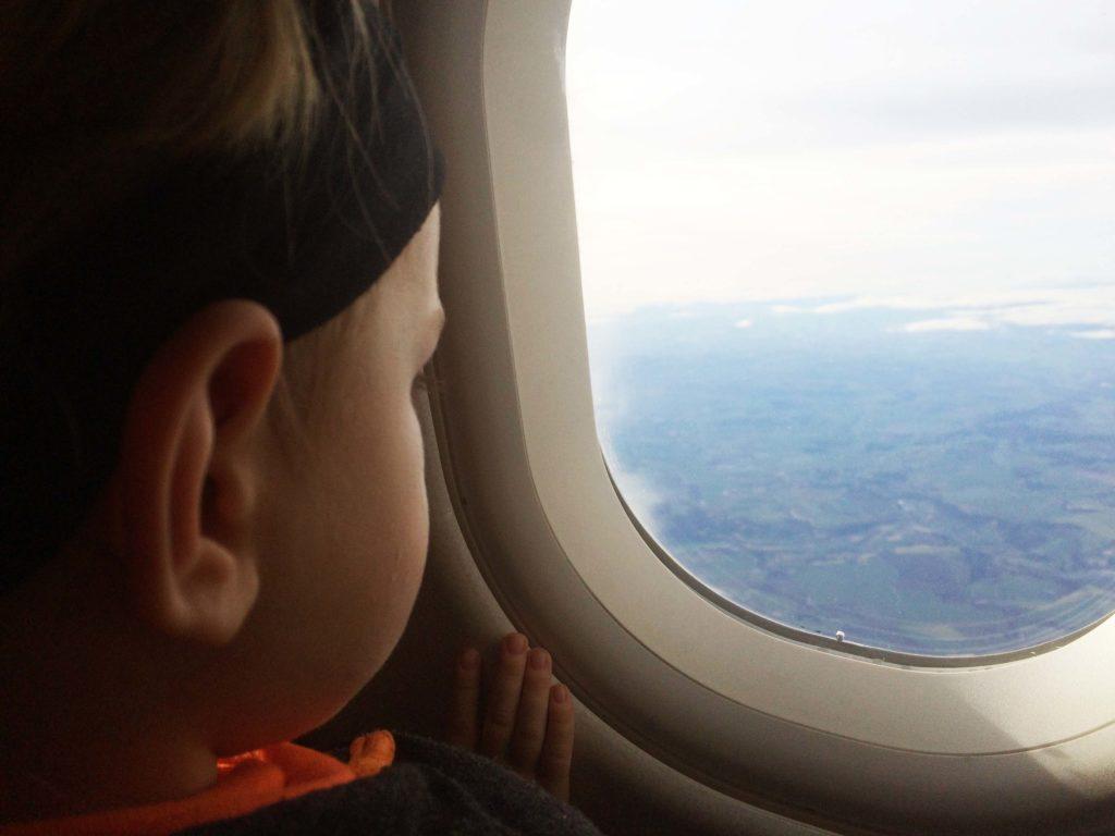 Kind schaut aus einen Fenster des Flugzeuges.