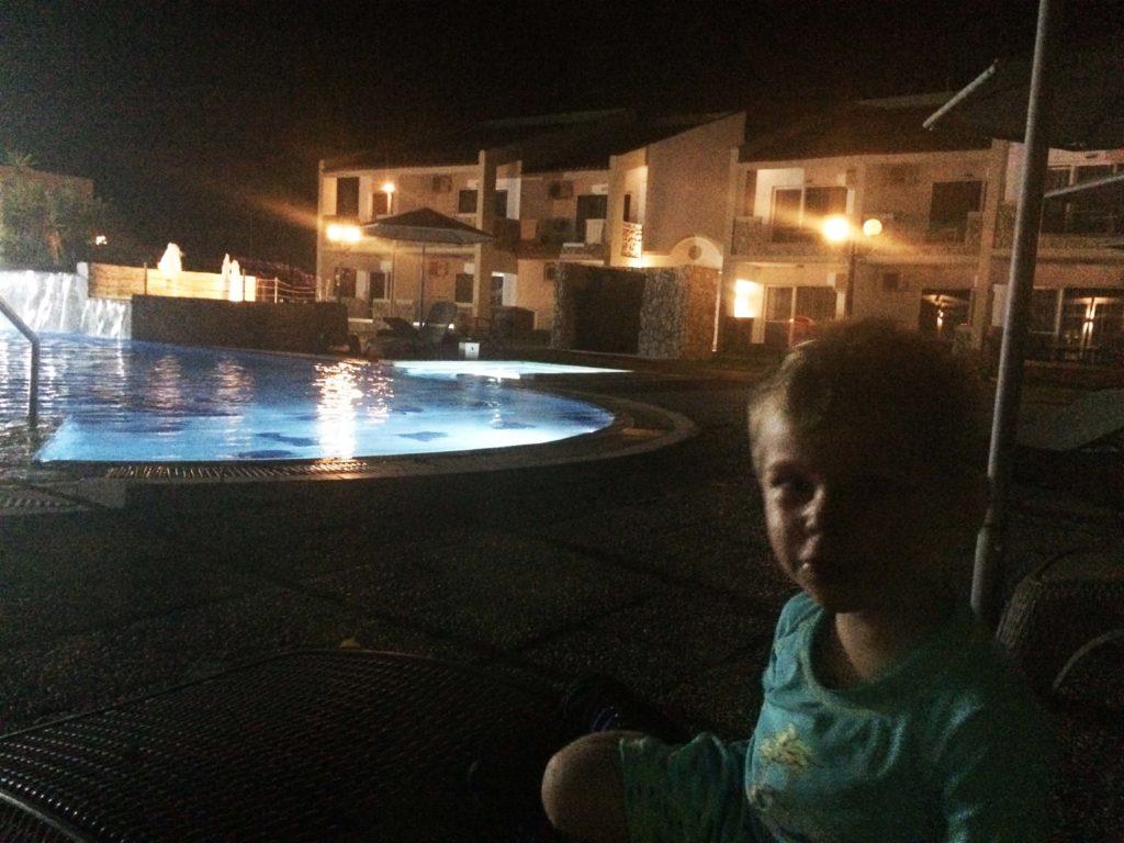 Kind sitzt abends im dunkeln am beleuchteten Pool. im Hintergrund sind die Unterkünfte zu sehen.