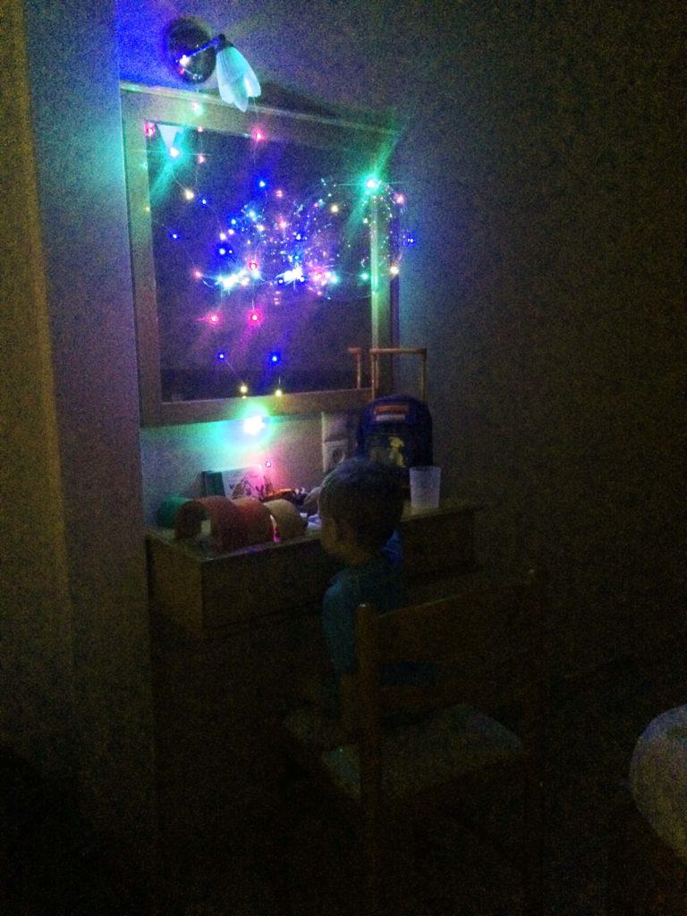 Kind spielt auf einer kleinen Kommode. Der Raum wird von einen LED Luftballon beleuchtet.