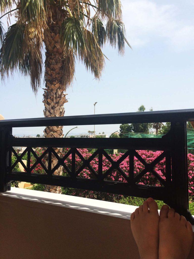Füße, die auf das Balkongeländer abgelegt wurden. im Hintergrund sieht man eine große Palme, Büsche mit rosa Blüten und einen blauen Himmel.