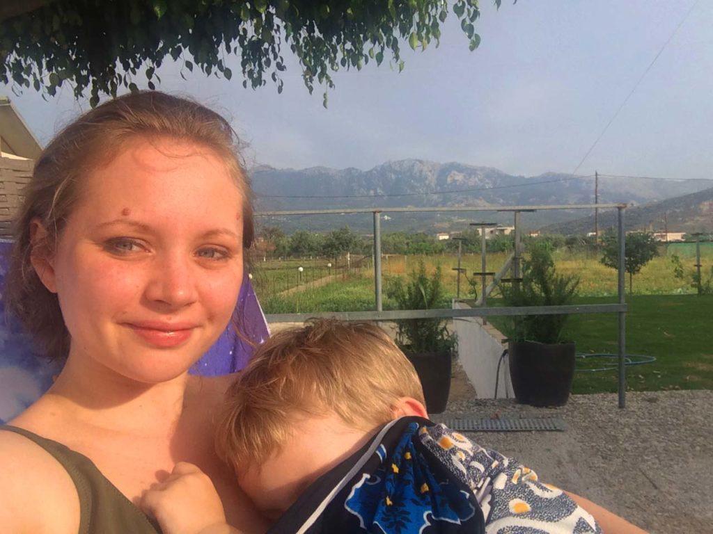 Mutter und Kind liegen auf einer Poolliege. Im Hintergrund ist ein großer Garten für Obst und Gemüse zu sehen. Dahinter ist das Dikeos Gebirge von Kos zu sehen.