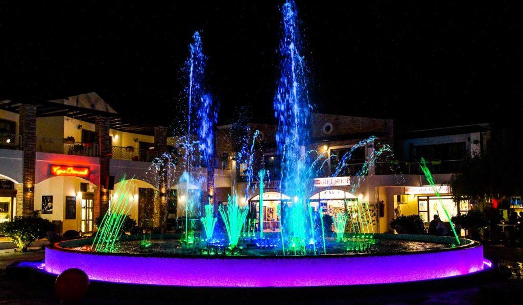 Bunt beleuchteter Springbrunnen in Tigkaki, Kos, Griechenland. Runderherum sind Bars und Live Musik.