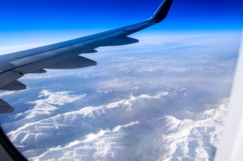 Blick aus dem Flugzeug während des Fluges nach Hurghada, Äygpten. Zu sehen ist blauer Himmel, Wolken und Berge