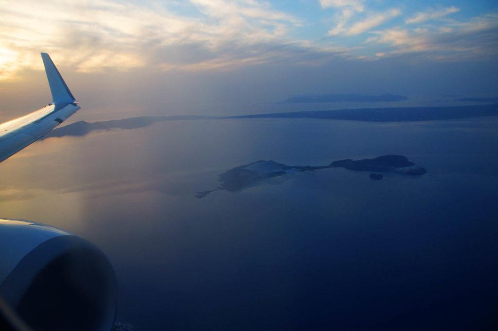 Blick aus dem Flugzeug: Man sieht eine Turbine und eine Tragfläche des Flugzeuges. Darunter das Meer mit griechischen Inseln und im Hintergrund einen blauen, wolkigen Himmel