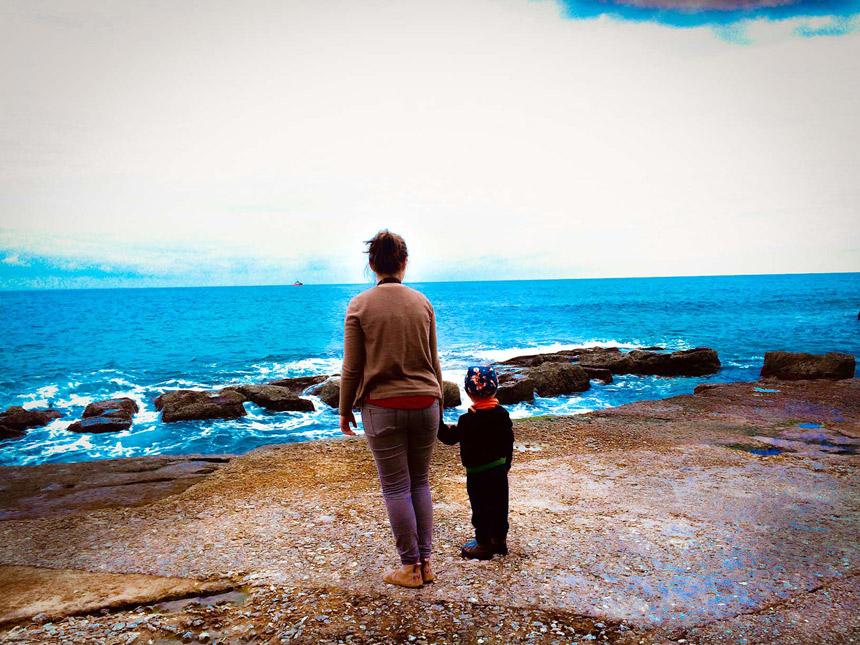 Mutter und Kind stehen Hand in Hand am Fond Ghadir Beach auf Malta und schauen aufs blaue Meer hinaus.