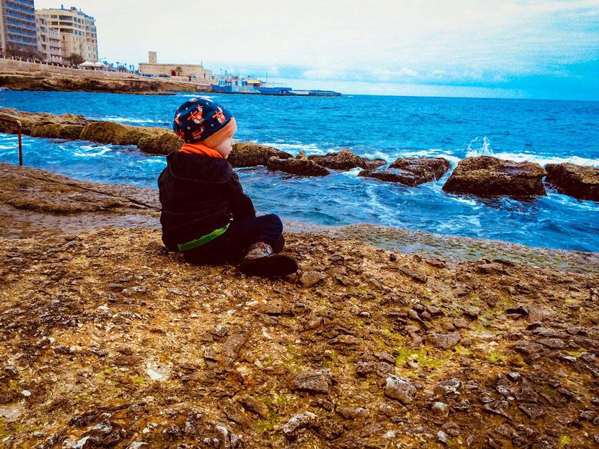 Kind sitzt am Strand des Fond Ghadir Beach auf Malta und schauts auf das Meer.