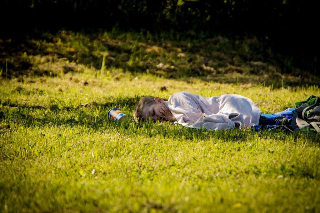 Kleines Kind schläft auf einer grünen Wiese im Schatten eines Baumes.
