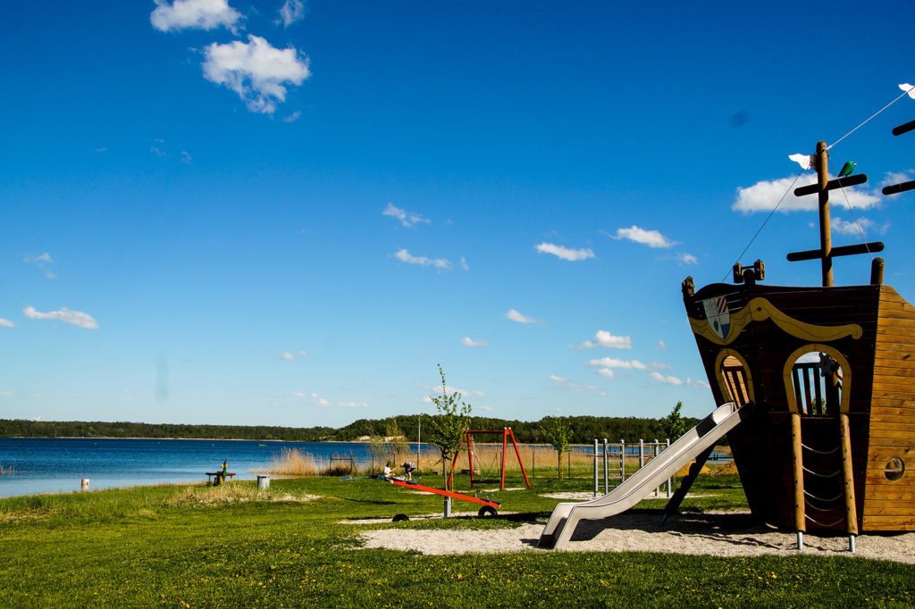 Der restliche Teil des Spielplatzes am Haselbacher See. Rutsche, Wippe, Kletterwand, Schaukel und Wasserspiel sind neben dem blauen Wasser zu sehen.