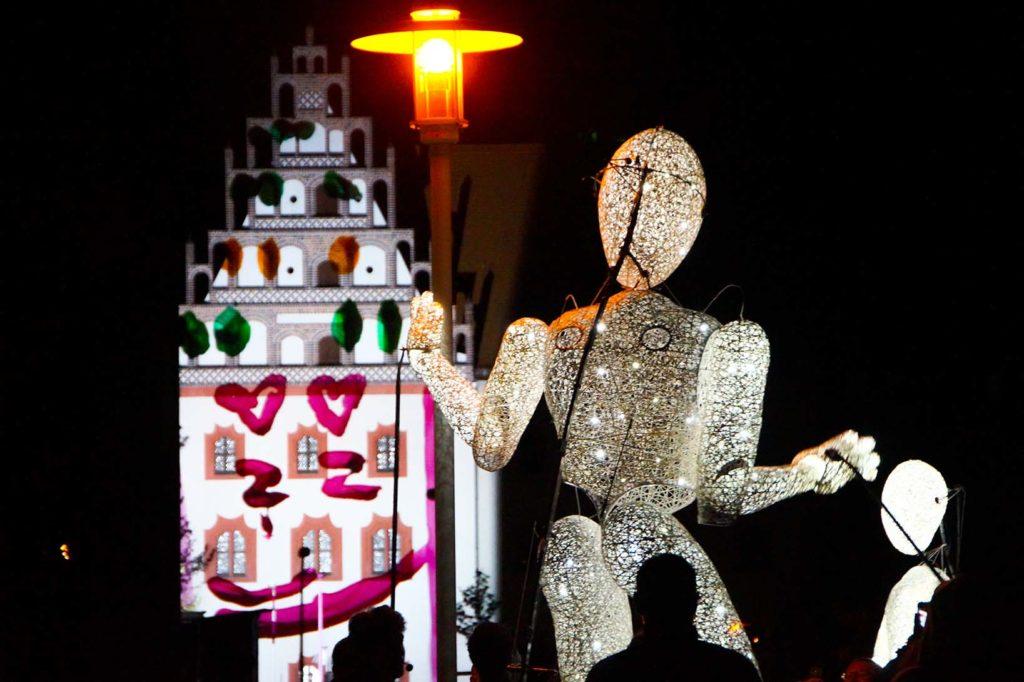 Weiß Leuchtende riesige Figur steht neben Straßenlaterne in Zwickau zum Lichterfest