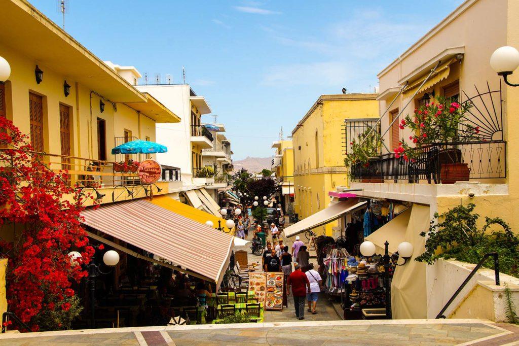 Shopping Passage in der Altstadt von Kos City, Griechenland. Der Himmel ist strahlend blau und die Häuser typisch mediterran.