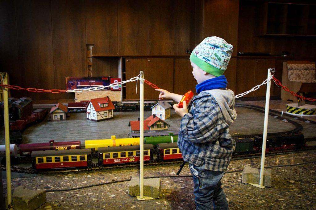 Kind steht vor einer aufgebauten Garteneisenbahn.