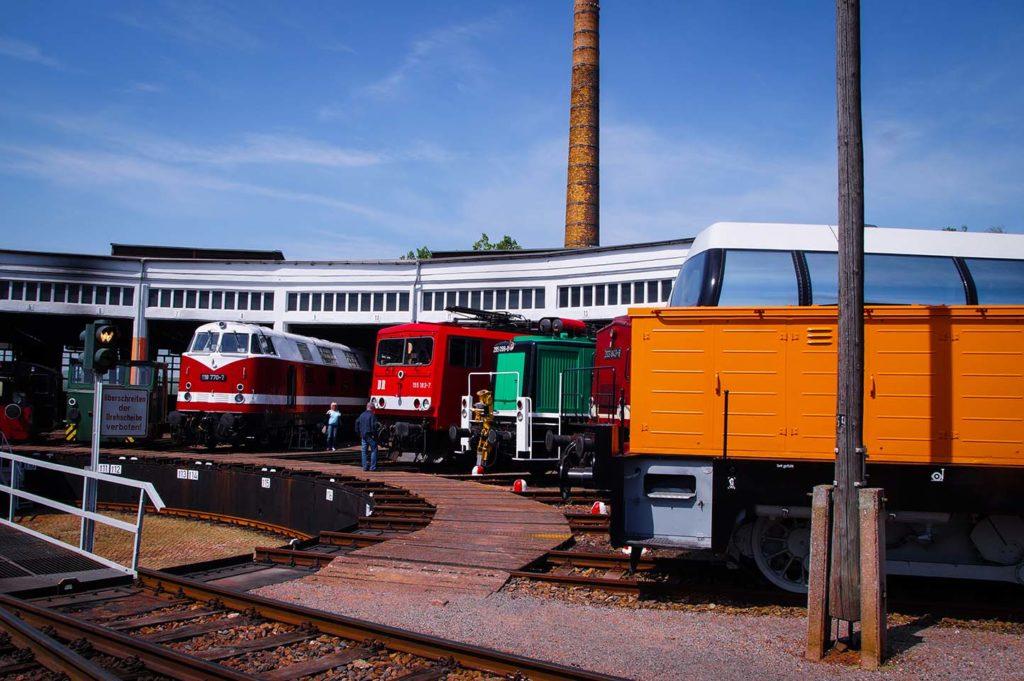 Sieben unterschiedlich alte Bahnen im Lokschuppen in Glauchau, Sachsen. Zu sehen sind verschiedene Elektro- und Dieselloks.