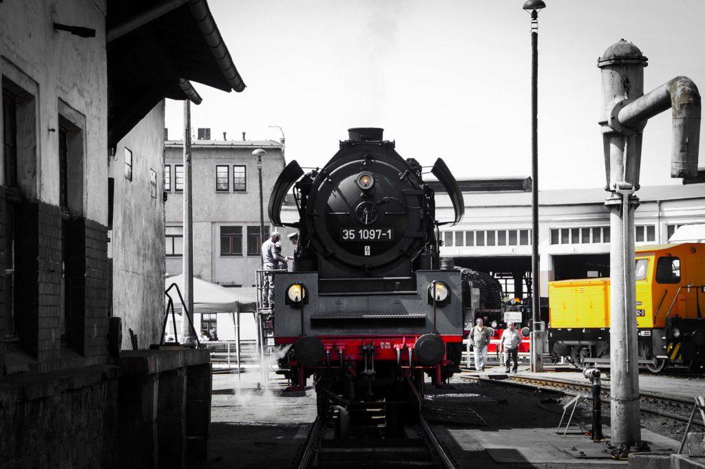 Alte schwarze Dampflok steht auf dem Gleis am Lokschuppen in Glauchau, Sachsen.