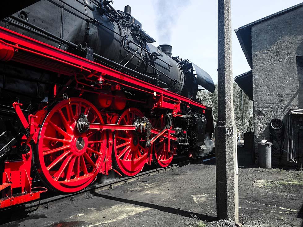 Alte schwarze Dampflok mit roten Rädern von der Seite zu sehen in Glauchau, Sachsen.