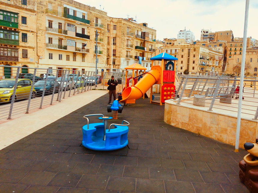 Spielplatz in Valetta, Malta. Zu sehen ist ein kleines blaues Karusell und eine große gelbe Röhrenrutschde. Dahinter die Wohnhäuser im typisch maltesischen Stil.