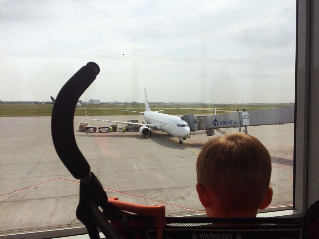 Kind schaut sich durch ein Fenster ein Fugzeug am Flughafen Leipzig Halle am Gateway an.