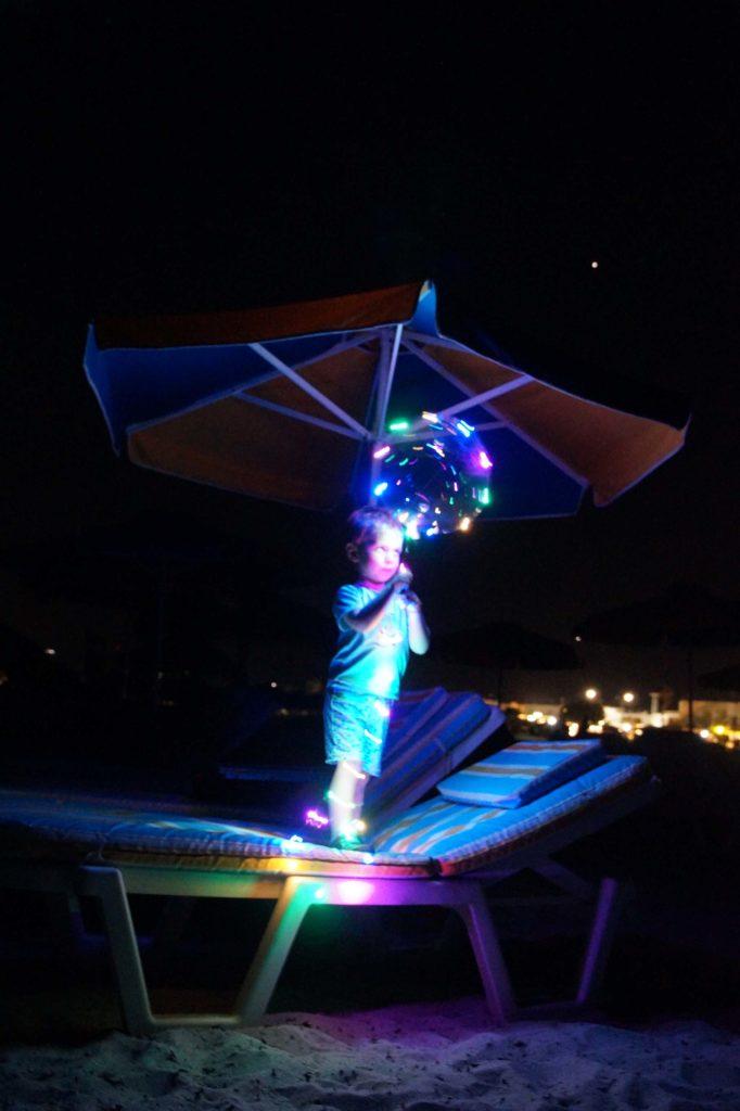Kind mit einem leuchtenden Luftballon nachts am White Beach von Tigkaki Kos Griechenland.