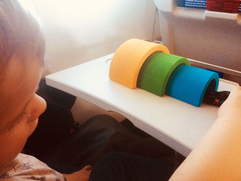 Kind spielt im Flugzeug mit kleinen Spielzeugautos und den Grimms Regenbogen auf dem ausklappbarem Tisch.