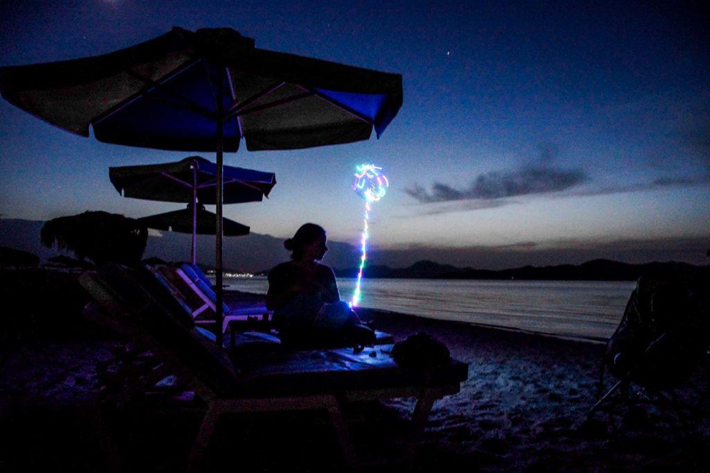 Mutter und Kind sitzen auf einer Liege am White Beach in Tigkaki Kos Griechenland und genießen den Sonnenuntergang. Der leuchtende Luftballon beleuchtet den dunklen Strand.