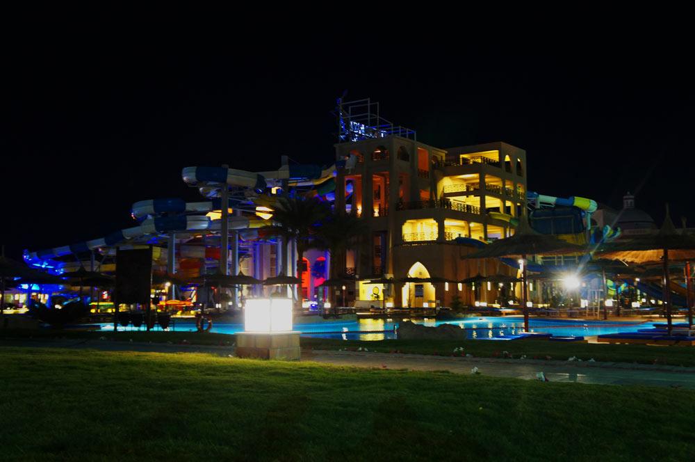 Nachts beleuchteter Rutschenturm des Albatros Aqua Park Resort.